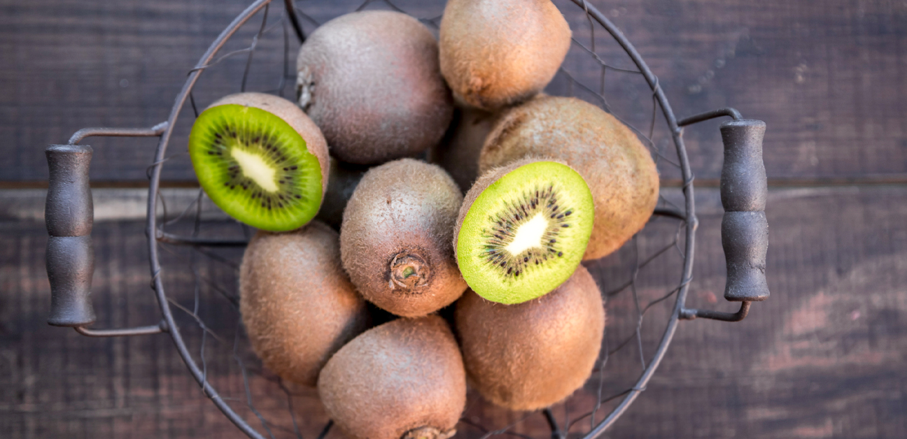 whole kiwi fruits and two kiwi halves in a metal basket with handles