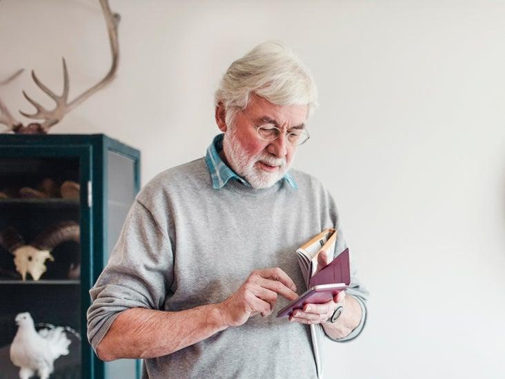 Senior man using mobile phone while standing by sofa 732X549 thumbnail.